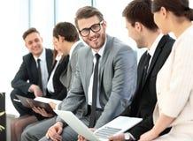 Счастливые бизнесмены говоря на встрече на офисе Стоковое фото RF