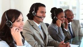 Счастливые бизнесмены используя их шлемофоны сток-видео