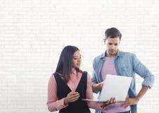 Счастливые бизнесмены используя компьютер против белой стены Стоковое фото RF