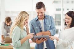 Счастливые бизнесмены используя цифровую таблетку Стоковое Изображение