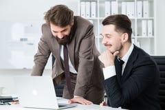 Счастливые бизнесмены обсуждая проект дела Стоковое фото RF