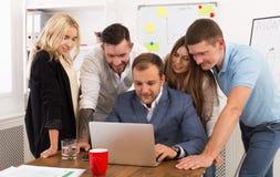 Счастливые бизнесмены объединяются в команду совместно взгляд на компьтер-книжке в офисе Стоковое фото RF