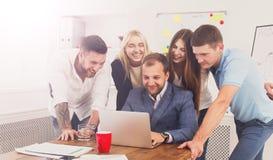 Счастливые бизнесмены объединяются в команду совместно взгляд на компьтер-книжке в офисе Стоковая Фотография RF