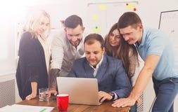 Счастливые бизнесмены объединяются в команду совместно взгляд на компьтер-книжке в офисе Стоковое Изображение