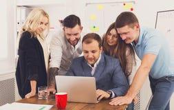 Счастливые бизнесмены объединяются в команду совместно взгляд на компьтер-книжке в офисе Стоковая Фотография
