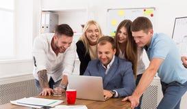 Счастливые бизнесмены объединяются в команду совместно взгляд на компьтер-книжке в офисе Стоковое Изображение RF