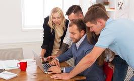 Счастливые бизнесмены объединяются в команду совместно взгляд на компьтер-книжке в офисе Стоковые Изображения RF