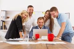 Счастливые бизнесмены объединяются в команду совместно имеют потеху в офисе стоковые изображения