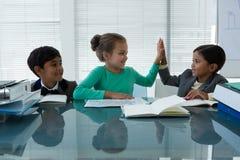 Счастливые бизнесмены работая в зале заседаний правления Стоковые Изображения RF