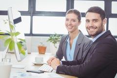 Счастливые бизнесмены работая на компьютере на столе Стоковые Изображения RF
