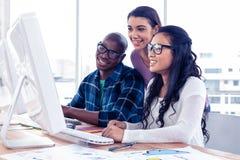 Счастливые бизнесмены работая на компьютере Стоковое Изображение