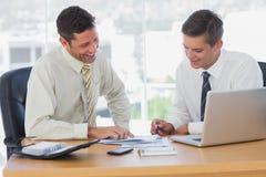 Счастливые бизнесмены работая совместно и усмехаясь Стоковое Изображение RF
