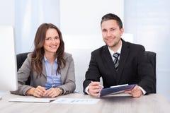 Счастливые бизнесмены сидя на столе держа доску сзажимом для бумаги Стоковые Фотографии RF