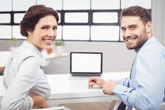 Счастливые бизнесмены сидя на столе компьтер-книжки Стоковая Фотография RF