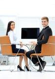 Счастливые бизнесмены смотря камеру в офисе и используя com Стоковые Изображения RF