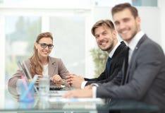 Счастливые бизнесмены смотря камеру в офисе и используя com Стоковое Фото