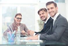 Счастливые бизнесмены смотря камеру в офисе и используя com Стоковое фото RF