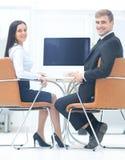 Счастливые бизнесмены смотря камеру в офисе и используя com Стоковая Фотография
