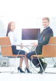 Счастливые бизнесмены смотря камеру в офисе и используя com Стоковые Фотографии RF