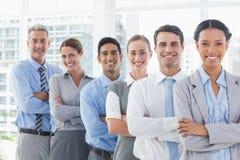 Счастливые бизнесмены смотря камеру в ряд Стоковые Изображения