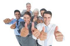 Счастливые бизнесмены смотря камеру с большими пальцами руки вверх Стоковая Фотография