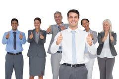 Счастливые бизнесмены смотря камеру с большими пальцами руки вверх Стоковая Фотография RF