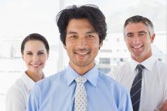 Счастливые бизнесмены смотря камеру Стоковая Фотография
