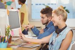 Счастливые бизнесмены смотря компьютер Стоковое Изображение