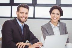 Счастливые бизнесмены с компьтер-книжкой в офисе Стоковые Изображения RF