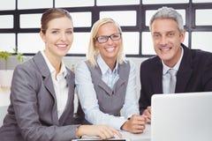Счастливые бизнесмены с компьтер-книжкой на столе Стоковое Изображение RF