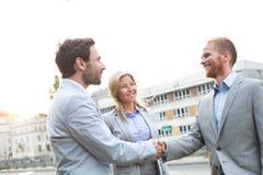 Счастливые бизнесмены тряся руки в городе против ясного неба Стоковое фото RF