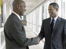 Счастливые бизнесмены тряся руки в коридоре офиса Стоковые Изображения RF