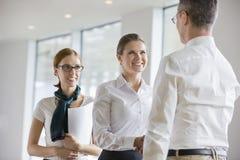 Счастливые бизнесмены тряся руки в офисе Стоковые Изображения