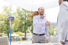 Счастливые бизнесмены тряся руки на внешнем ресторане Стоковое Изображение RF