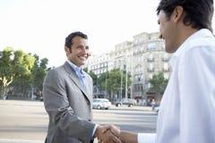 Счастливые бизнесмены тряся руки на улице города Стоковое Изображение