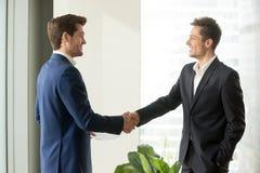 Счастливые бизнесмены тряся руки стоя в офисе, герметизировать хороший Стоковая Фотография RF
