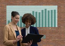 Счастливые бизнес-леди используя таблетку против кирпичной стены с графиками Стоковые Фото