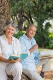 Счастливые более старые книги чтения пар совместно сидя на стволе дерева Стоковая Фотография