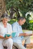 Счастливые более старые книги чтения пар совместно сидя на стволе дерева Стоковое Фото