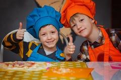 Счастливые 2 брать в кухне Дети подготавливая пиццу Стоковые Изображения RF