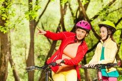 Счастливые велосипедисты выбирая путь пути на солнечном парке Стоковая Фотография RF