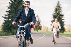 Счастливые велосипеды катания семьи в парке Стоковое Фото