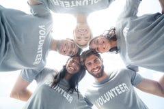Счастливые волонтеры формируя груду стоковое фото