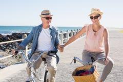 Счастливые вскользь пары идя для велосипеда едут на пристани Стоковые Фотографии RF