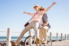 Счастливые вскользь пары идя для велосипеда едут на пристани Стоковое Фото