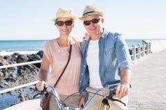 Счастливые вскользь пары идя для велосипеда едут на пристани Стоковые Фото
