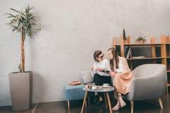 Счастливые гомосексуальные пары используя smartphone и выпивая кофе в кафе Стоковое Изображение RF