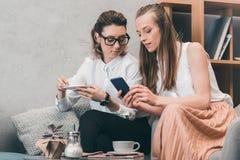 Счастливые гомосексуальные пары используя smartphone и выпивая кофе в кафе Стоковые Изображения RF