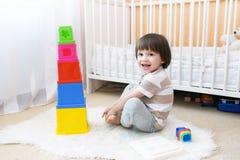 Счастливые 2 года мальчика играют воспитательную игрушку дома Стоковое Изображение RF