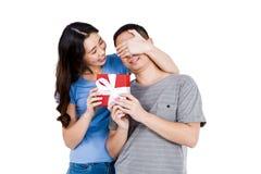 Счастливые глаза парня заволакивания женщины пока gifting Стоковое Изображение